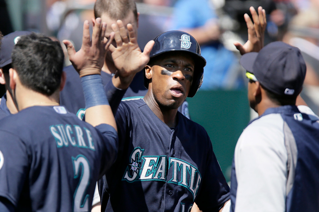 . Seattle Mariners\' Austin Jackson celebrates in the dugout after scoring in the sixth inning of a baseball game against the Detroit Tigers, Sunday, Aug. 17, 2014, in Detroit. (AP Photo/Duane Burleson)
