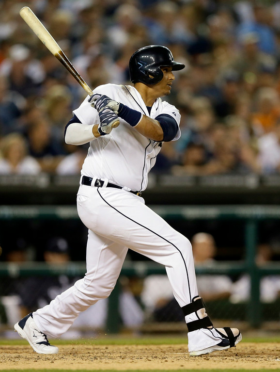 . Detroit Tigers\'  Victor Martinez follows through on an RBI single during the seventh inning of an interleague baseball game against the Colorado Rockies, Friday, Aug. 1, 2014, in Detroit. (AP Photo/Carlos Osorio)