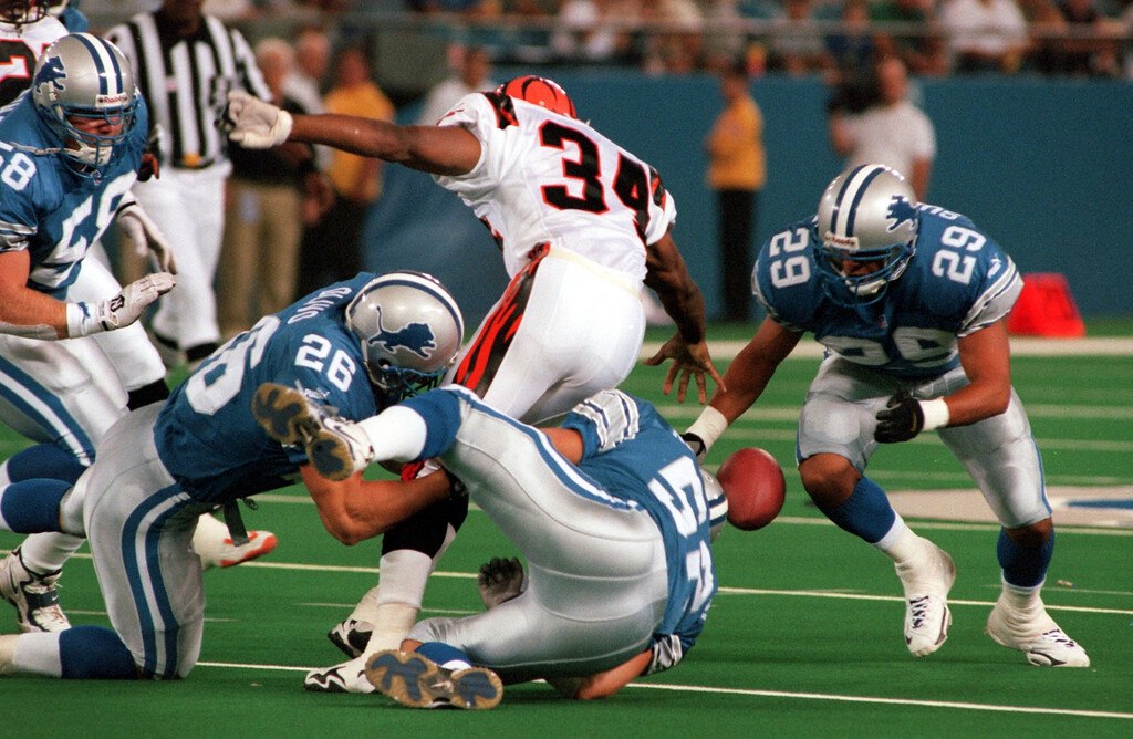 . Tremain Mack (34) of the Cincinnati Bengals fumbles the football as Detroit Lions defence lead by Clint Kriewaldt (58), Brock Olivo (26) and RonRice (29) scramble to recover in the first half during Friday night\'s preseason home opener against the Cincinnati Bengals.