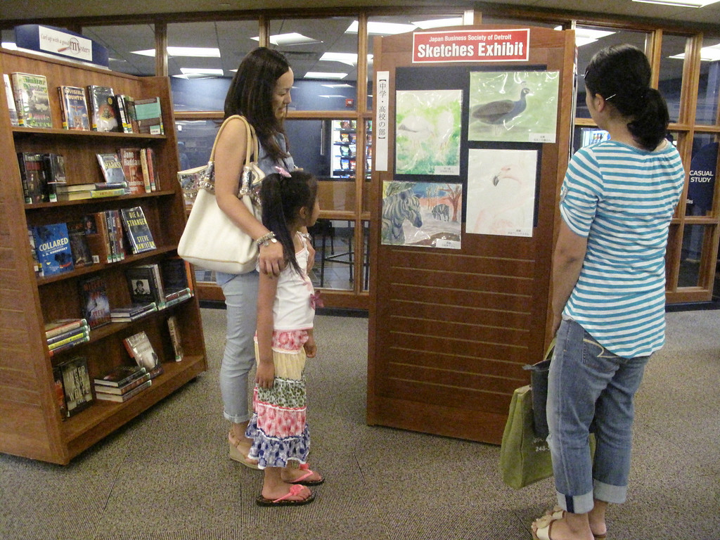 . Kazuko Hayashiand, with daughter Sarah Hayashi, and Naomi Murata, all of West Bloomfield, scan zoo animal drawings made by members of the metro area Japanese community. The drawings, at the West Bloomfield Township Main Library, will greet eight teens from Awaji City, Japan on July 31 when they stop by as part of a U.S. visit.