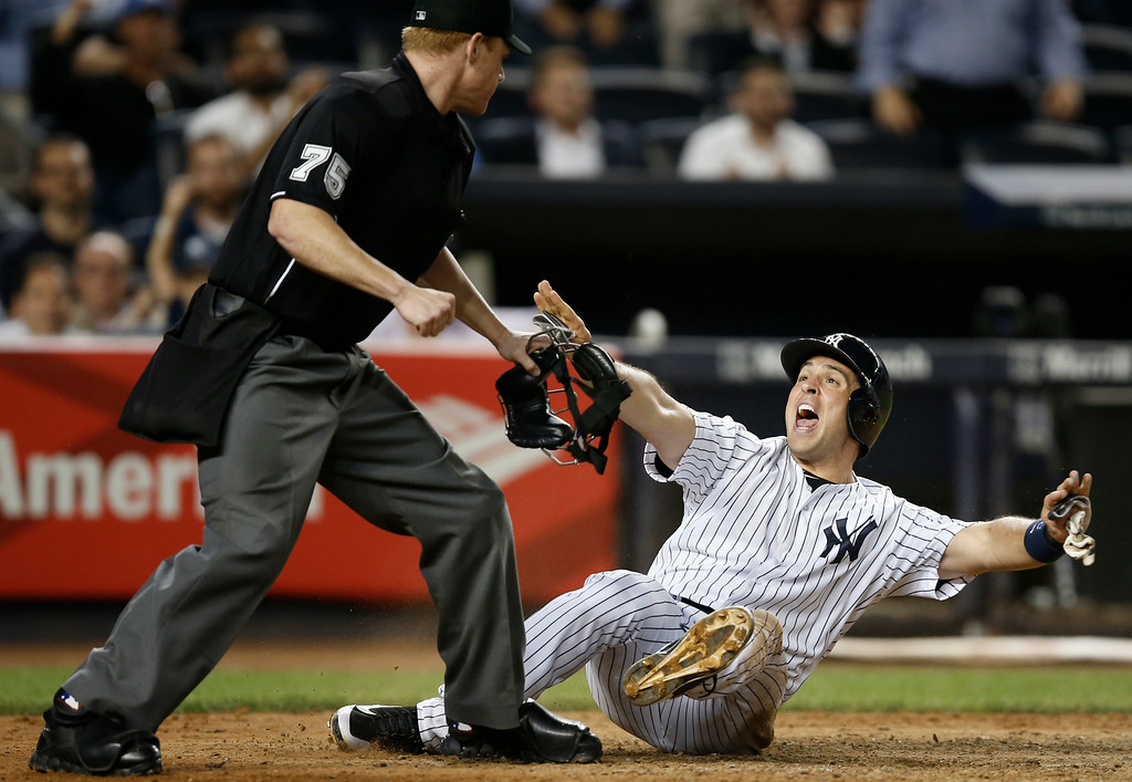 . New York Yankees Mark Teixeira protests as home plate umpire Tom Woodring (75) rules him out in an eighth-inning play at the plate in a baseball game against the Detroit Tigers at Yankee Stadium in New York, Wednesday, Aug. 6, 2014.  Teixiera was later ruled safe in a video review, but injured his hand on the play and was removed from the game. (AP Photo/Kathy Willens)