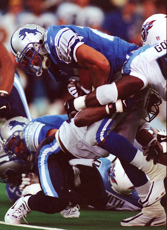 . Detroit Lions running back Lamont Warren (center) gains yardage as he is wrapped up by Tennessee Titan Randall Godfrey (right) and another defender during the Lions 27-24 loss at the Pontiac Silverdome Sunday.