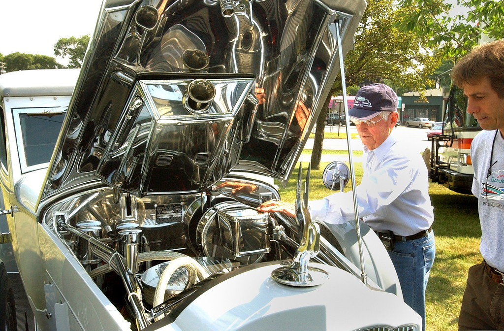 . John McMullen of Lapeer, shows off the engine of his \'33 Parkard Town Car. McMullen\'s car was on display at the kickoff of the 10th anniversary of the Woodward Dream Cruise.