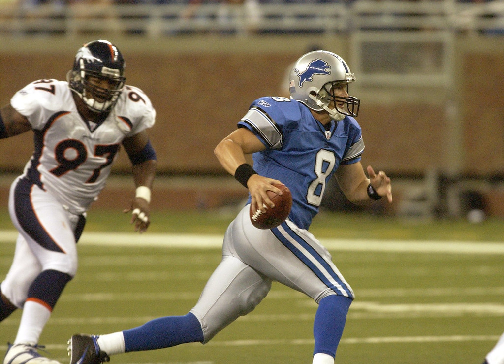 . Lions starting QB Jon Kitna scrambles for a first down during the first quarter as Bronco \'s #97 Demetrin Veal chases from behind. The Oakland Press/DOUG BAUMAN