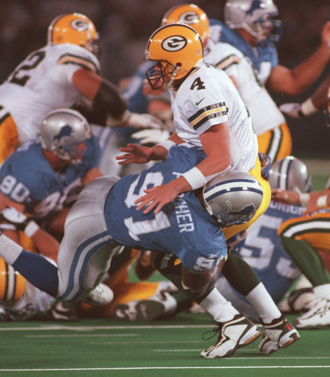 . Detroit Lions defenseman Robert Porcher (bottom, #91) knocks down Green Bay Packers quarterback Brett Favre (#4) in the second quarter, Thursday, October 15, 1998.