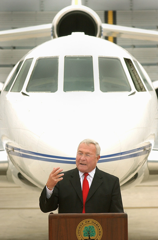 . Oakland County Executive L. Brooks Patterson stands in front Falcon Jet during the dedication of the Ground Run-up Enclosure at the Oakland County International Airport in Waterford Township.