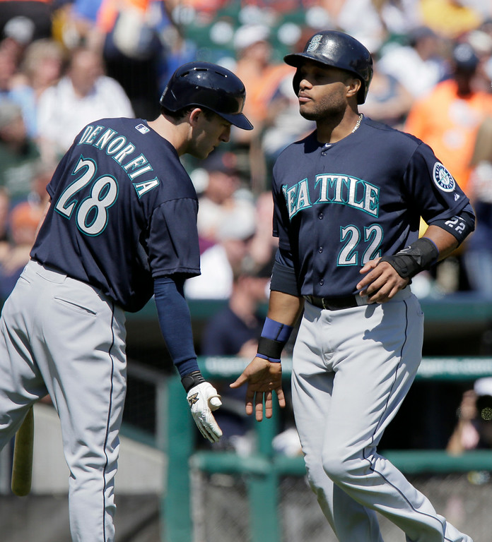 . Seattle Mariners\' Robinson Cano (22) is congratulated by Chris Denorfia (28) after scoring on a single by Kyle Seager during the sixth inning of a baseball game against the Detroit Tigers, Sunday, Aug. 17, 2014, in Detroit. (AP Photo/Duane Burleson)
