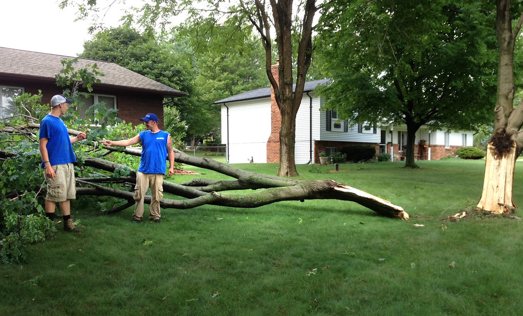 . Geoffrey Zinn, left, and Mike Layou with a big branch down in Brandon Township, near Sashabaw and Seymour Lake Roads.  The Oakland Press/CAROL HOPKINS