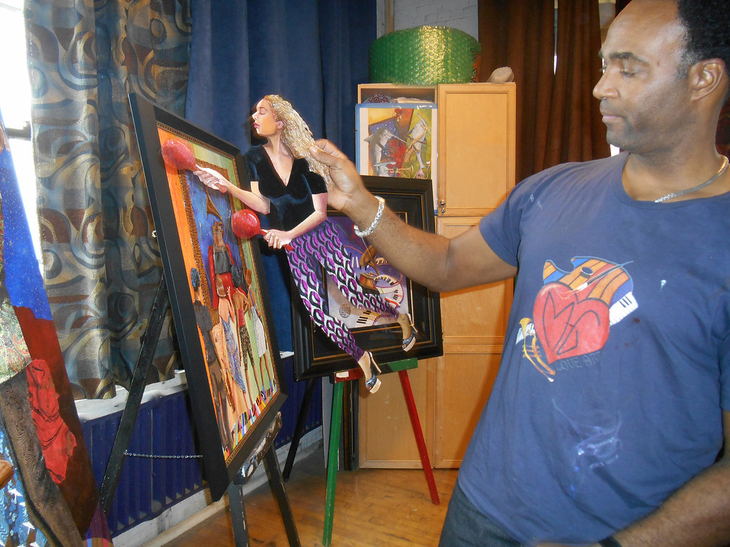 . Marcus Glenn holds up a Flat Life cutout from one of his pictures, which he was working on. He uses his characters like paper dolls and arranges them before finalizing the pictures. This character is based on his wife, Yolanda. Photo by Nicole M. Robertson