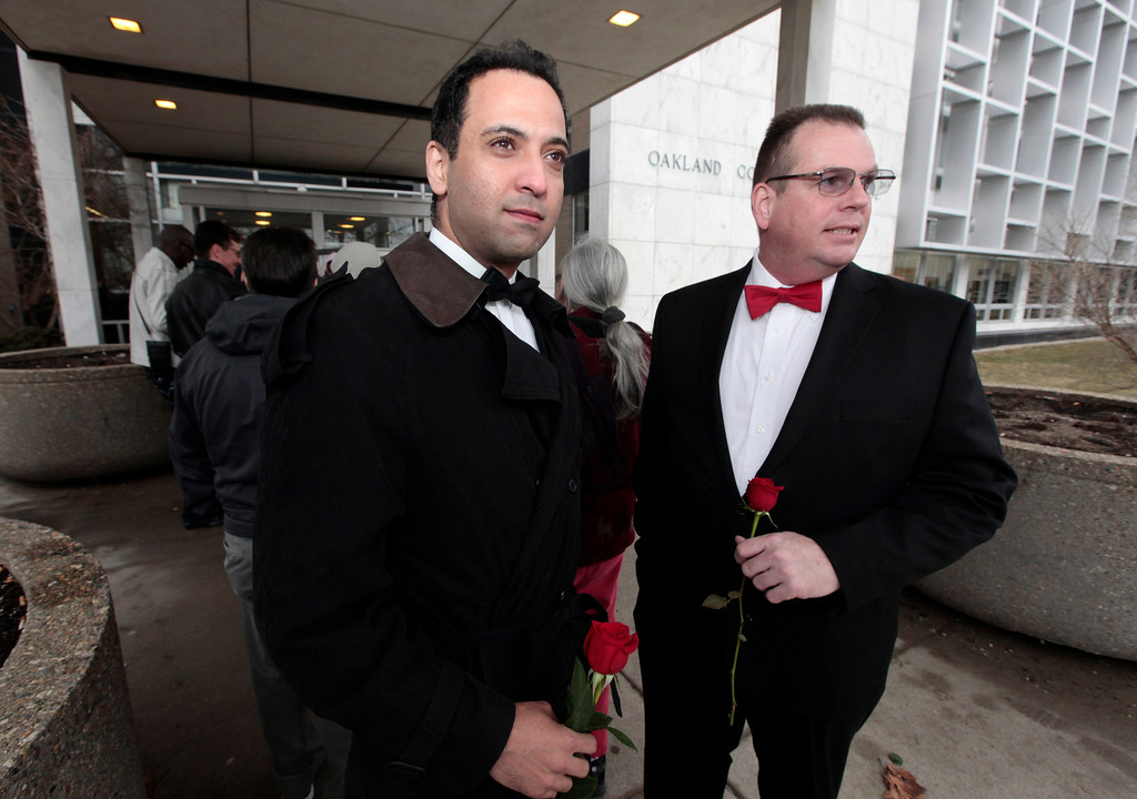 . Nasir Khawaja, left, and Mark Sarver stand outside in line to apply for a marriage license at the Oakland County Clerks office in Pontiac, Mich., Saturday, March 22, 2014. A federal judge has struck down Michigan\'s ban on gay marriage Friday the latest in a series of decisions overturning similar laws across the U.S. Some counties plan to issue marriage licenses to same-sex couples Saturday, less than 24 hours after a judge overturned Michigan\'s ban on gay marriage. (AP Photo/Paul Sancya)