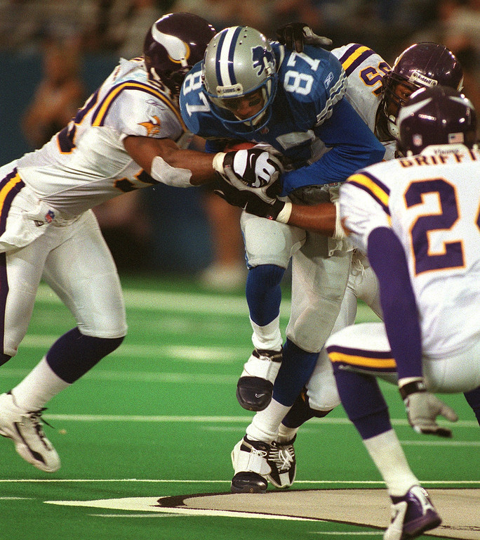 . Detroit Lions wide receiver Johnnie Morton (center) busts through Minnesota defenders Lance Johnstone (left) and Lemanski Hall (right)to gain ground in the Lions\' 27-24 victory over the Minnesota Vikings at the Silverdome Sunday.  The Lions are now 1-12.