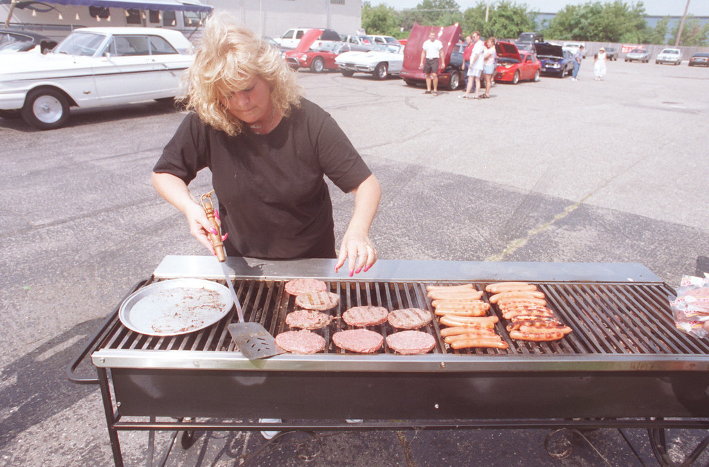 . Shila Morganroth of Highland flips burgers & hot dogs in Pontiac along woodward ave. Dream Cruise celebration.