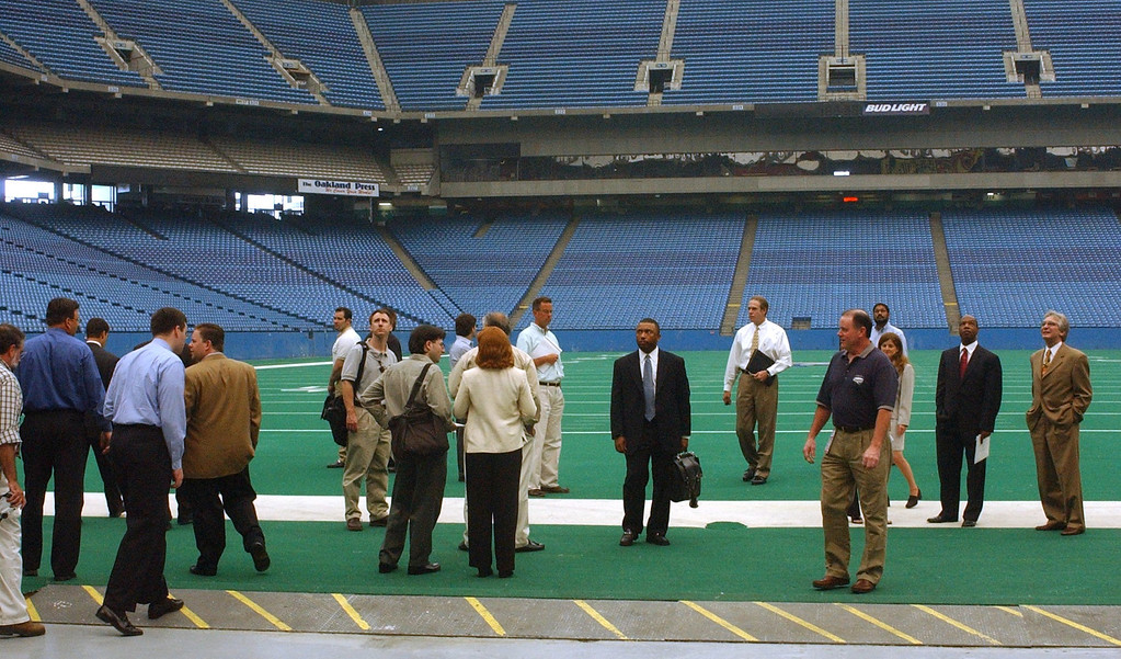 . John Kissick, dark short sleve shirt right, director of operations at the Pontiac Silverdome leads a group onto the Detroit Lions playing field during a walking tour of the faculity on Monday. The city of Pontiac and Pontiac Silverdome officals are soliciting offers for the property, since the Detroit Lions vacated the property for their new $315 million indoor venue located in down town Detroit.