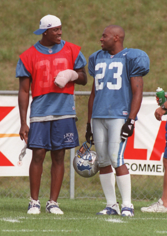 . Detroit Lions injured cornerback Bryant Westbrook (left, #32) chats with teammate Terry Fair (#23) during practice, Monday, August 9, 1999.