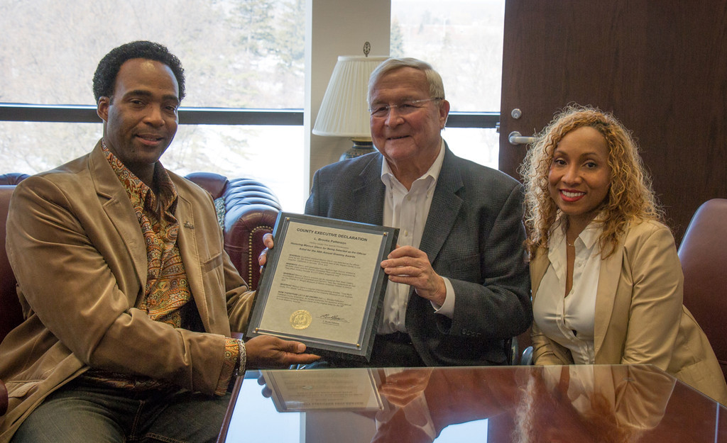 . Marcus and his wife, Yolanda, receive recognition from Oakland County Executive L. Brooks Patterson at his Waterford Township office. Photo courtesy of Park West Gallery