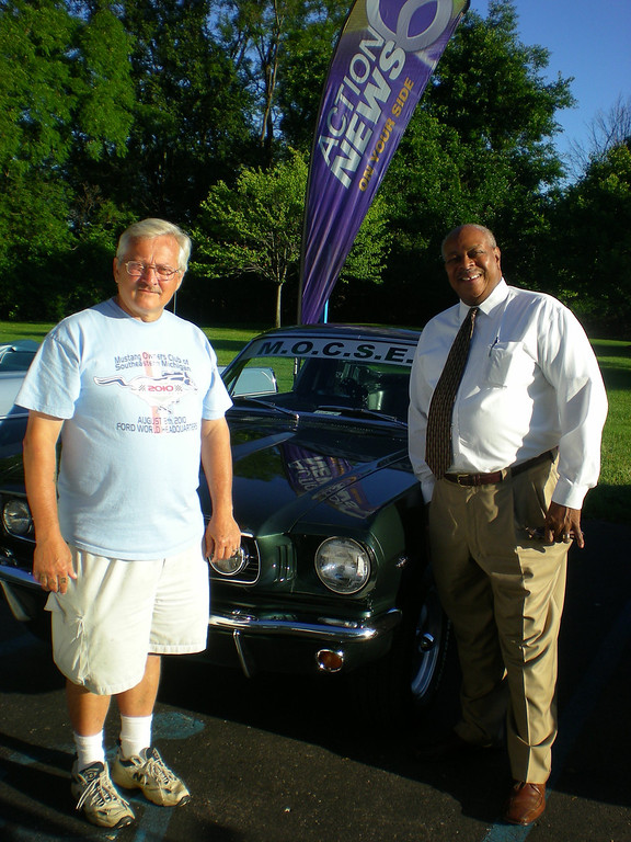 """. Mike Sove of Southfield (left) shows off his 1966 Mustang fastback to Woodward Dream Cruise board member, the Rev. Douglas Jones of Pontiac, at a gathering of the Dream Cruise board Monday at WXYZ-TV in Southfield. Sove, regional director of the Mustang Club of America, will have his car at Nine Mile and Woodward in \""""Mustang Alley\"""" on Saturday."""