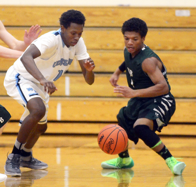 . Waterford Mott\'s #11 Austin Sherrell and West Bloomfield\'s #1 Michael King go after a loose ball during their game at Waterford Mott High School, Thursday December 12, 2013.  West Bloomfield went on to win the game 55-52. (Vaughn Gurganian-The Oakland Press)