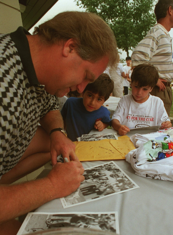. Eric Hipple former Detroit Lions QB signing autographs for thoes on hand at the Fun Run/Walk fundraiser to help raise money for juvenile diabetes. Jacob Rosenberg 5 yrs old and Jared Grodman 5 yrs old with Hipple. The fundraiser started 4 years ago by Dr. Scott Grodman and wife Karyn whose two kids have the desease hope to raise $10,000.
